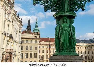 dark green street lamp with figures in Hradčany in Prague - Czech Republic