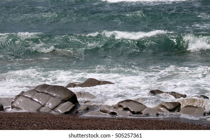 Dark green water of the wild atlantic ocean at the coast, with old grey weathered and glossy stones, shining in the sun shine