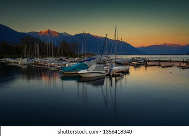 Dark green and yellow sunset with boats in the port of Ascona, Switzerland
