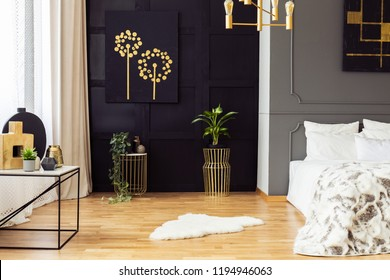 Dark grey bedroom interior with fur rug, gold accessories, simple painting and window with curtains in the real photo
