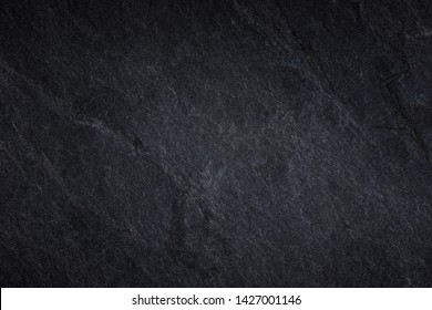 Dark grey black slate background or natural black stone texture. pattern of stone wall and floor