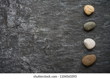Dark grey black slate stone background with zen stones in luxury asian spa