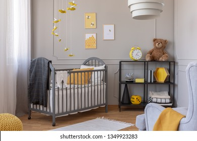Dark grey blanket on wooden crib in yellow and grey baby bedroom with armchair and industrial metal shelf with toys