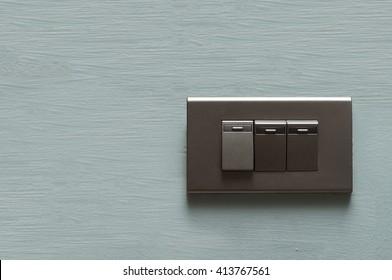 Dark grey light switch on blue interior wall. Dark grey light switch with copy space.