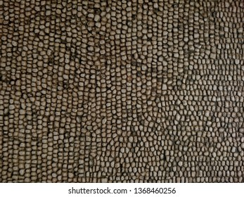 Dark grey old cobblestone block pavement texture background. Old historic cobblestone pebble pavement pattern background. Street floor path brown cobblestone tile pavement as brick wall or floor tile
