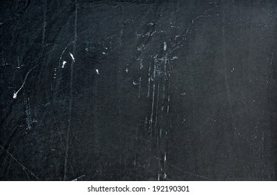 Dark grey stone background with cracks and scratches