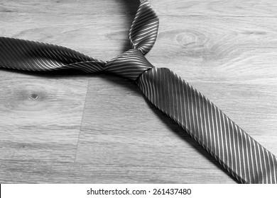 Dark grey tie on the floor in black and white