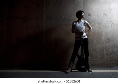 dark grunge style asian rock star holding a guitar