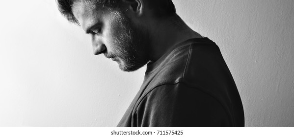 Dark guy, man  profile, tilted his head down in depression on a white background isolated,  black and white