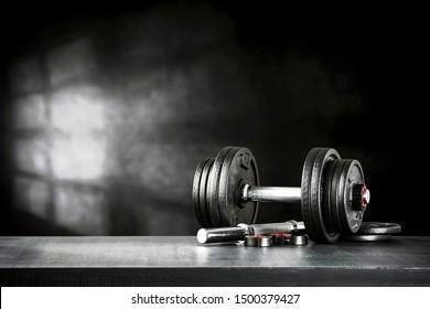 Dunkles Fitnesscenter mit schwarzen Hantel