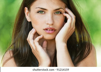 dark hair and beautiful sexy girl with bare shoulders seductively posing with his hands touching face