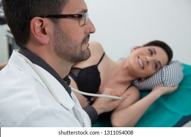 dark hair doctor listening to his female patient with a ultrasound ecography in a medical room using a medical computer