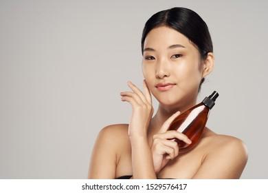 Dark hair lotion in a jar naked shoulders beige background beautiful woman narrow eyes