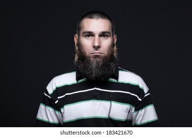 Dark haired, bearded man on a black bakground