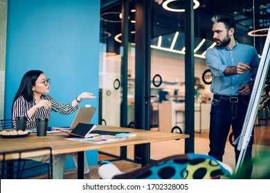 Dark haired bearded man in shirt and jeans explaining business strategy to Asian woman in glasses and striped white and black shirt