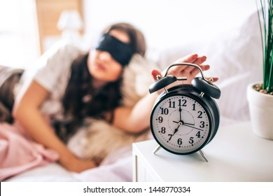 Dark haired beautiful young brunette wake up in her bed. Sleepy woman in black mask reaching hand to clock. Turn off. Lying on bed in morning. Bedroom.