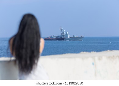 Dark haired female person observing floating military ship. Rear view of young woman with loose hair standing on seafront. Focus on background