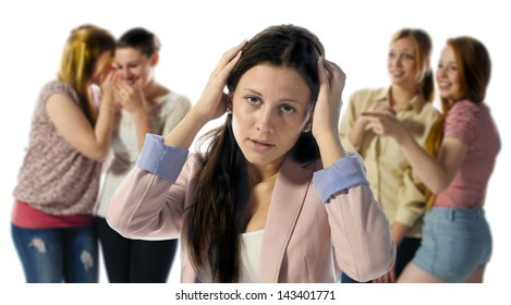 A dark haired girl is desperate and holds his hands to his head in the background are out of focus four girls who laugh at them.