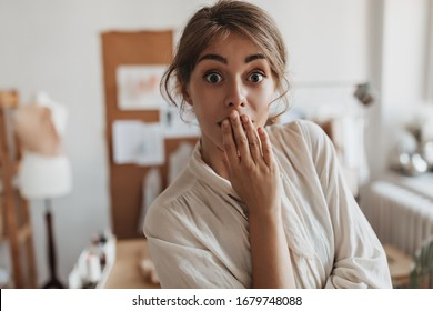 Dark haired lady looks into camera in surprise. Shocked woman in white blouse poses in office and covers her mouth