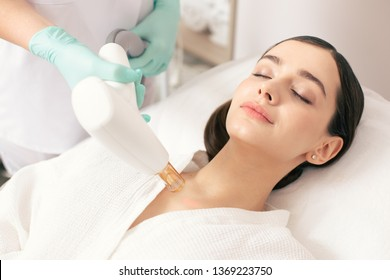 Dark haired lady lying with closed eyes while a professional medical worker holding a modern tool and removing scars with a laser