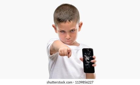 Dark haired little child holding broken smartphone pointing with finger to the camera and to you, hand sign, positive and confident gesture from the front
