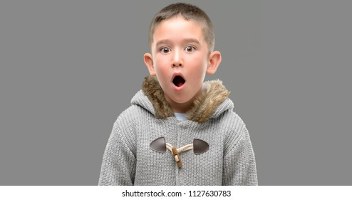 Dark haired little child wearing a coat scared in shock with a surprise face, afraid and excited with fear expression