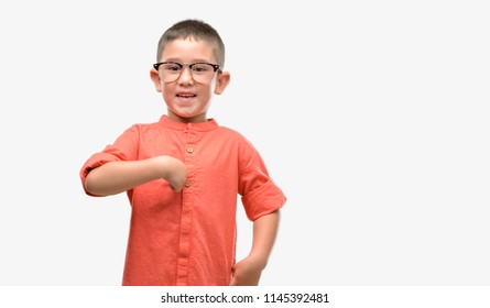 Dark haired little child wearing glasses with surprise face pointing finger to himself