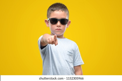 Dark haired little child wearing sunglasses pointing with finger to the camera and to you, hand sign, positive and confident gesture from the front