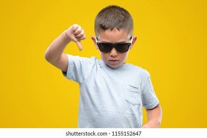 Dark haired little child wearing sunglasses with angry face, negative sign showing dislike with thumbs down, rejection concept