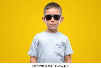 Dark haired little child wearing sunglasses with a confident expression on smart face thinking serious