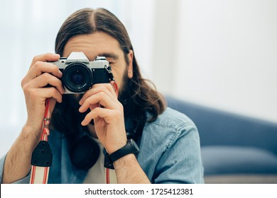 Dark haired man in jeans shirt taking photos with his film camera