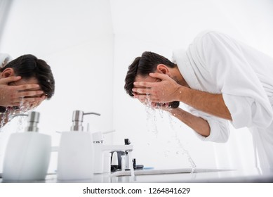 Dark haired man in white bathrobe bending his back and putting both hands on his face while washing it over the sink