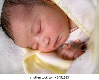 a dark haired one day old baby peacefully sleeping