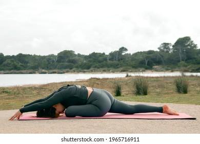 Cabeza oscura, mujer blanca caucásica haciendo estiramientos y respiración antes de practicar yoga o pilates, Hanumanasana (pose de Dios del mono)