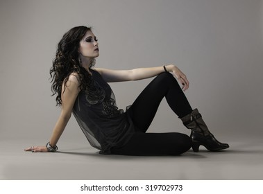 Dark haired woman seated on ground, wearing edgy grunge style outfit leaning with her wrist on her knee.