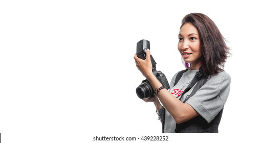 Dark haired woman taking a photo with a modern camera with flash on a white background
