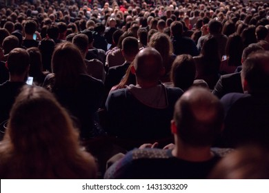In the dark hall there is a view from the back of a crowd of hundreds of people sitting and watching the screen in a movie theater or performing on stage.