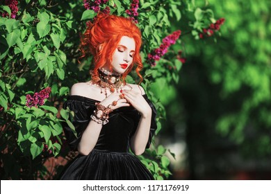 Dark halloween attire. Goth woman with pale skin and red hair in black edwardian gown and renaissance bracelet on hand. Pale girl witch with red lips. Goth look. Edwardian bracelet for halloween.