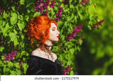 Dark halloween attire. Goth woman with pale skin and red hair in black victorian gown. Girl witch with red lips. Goth look. Victorian necklace for halloween.