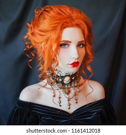 Dark halloween attire. Gothic woman vampire with pale skin and red hair in black dress and baroque necklace on neck. Girl witch with red lips. Gothic look. Baroque outfit for halloween. Clean skin.