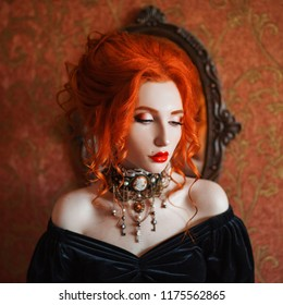 Dark halloween attire. Redhead gothic woman is vampire with pale skin in a black edwardian dress and a necklace on neck. Edwardian redhead girl witch with red lips. Gothic look. Outfit for halloween.