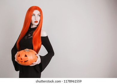 Dark halloween costume. Gothic woman vampire with pale skin and red hair in black dress holding pumpkin. Girl witch with red lips. Gothic look. Scary halloween pumpkin lantern.