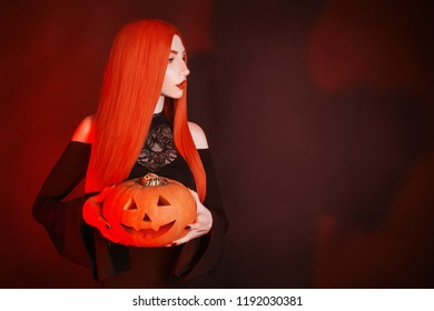 Dark halloween costume. Scary witch with red lips in hell. Gothic woman vampire with pale skin and red hair in black dress holding pumpkin. Gothic look. Scary halloween pumpkin lantern. Spooky hell