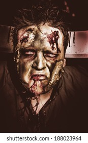 Dark halloween portrait of a scary zombie with blood gashing from monster mouth and carving knife in head