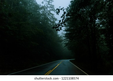 A dark highway cuts through an eerie and foggy mountain right before dusk