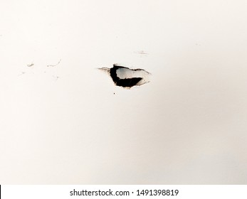 Dark Hole in the Wall on White Drywall Showing Major Damage Needing Repair in a Garage or Other Space