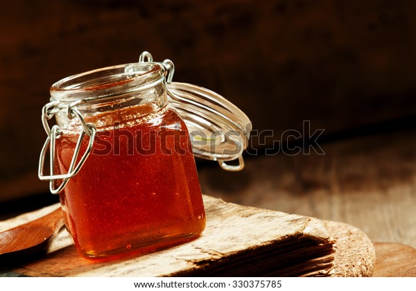 Dark honey from alpine herbs in a glass jar with a lid on old wooden background in rustic style, selective focus