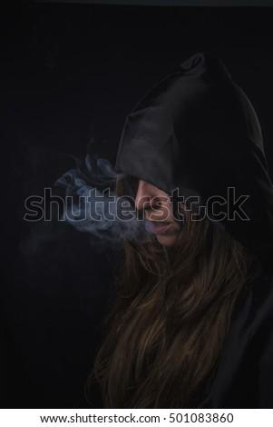 Dark hooded woman assassin