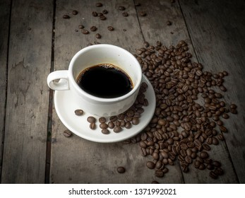Dark hot coffee cup on the wood table and have coffee beans.