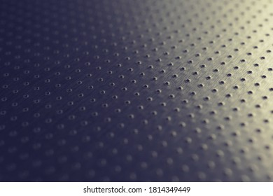 Dark industrial metallic background. Tinted blue and yellow wallpaper. Perforated aluminum surface with many holes. Perforation rows go into the distance and form a perspective. Macro